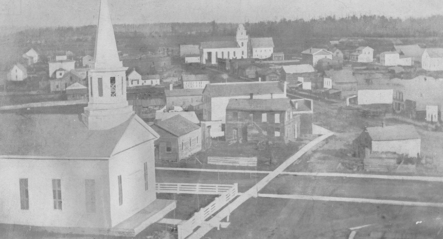Black and white photo of Lapeer in 1854, showing church house and other buildings